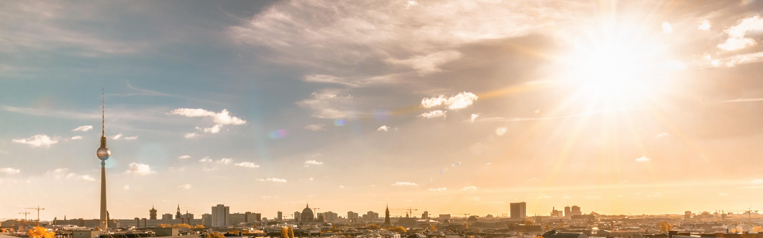 Blick über die Dächer von Berlin, viel leicht bewölkter Himmel. Links der Fernsehturm, rechts die blendende Sonne.